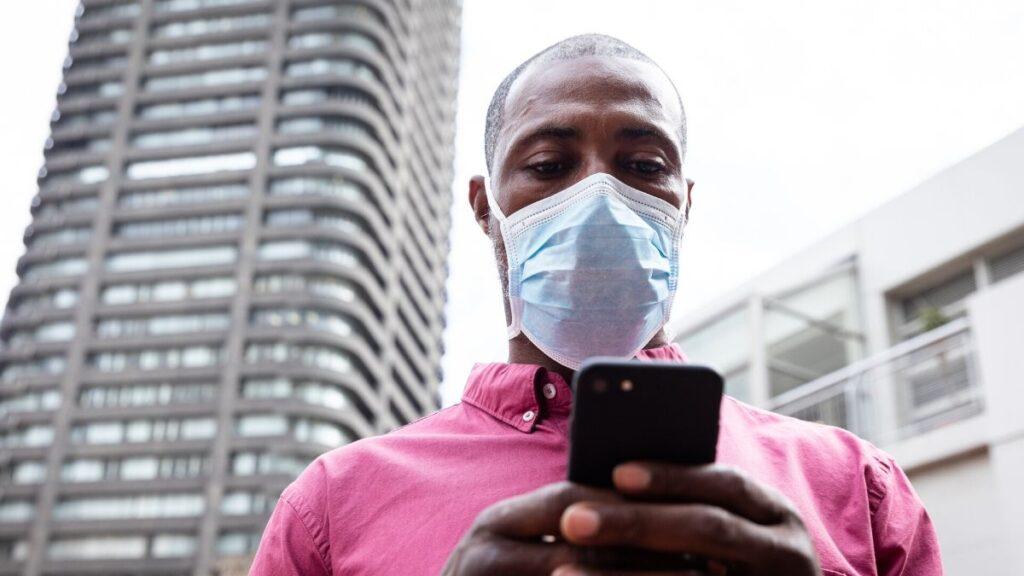 Homem segurando um celular de máscara